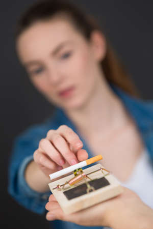 Lady reaching for cigarette on mousetrap Stock Photo
