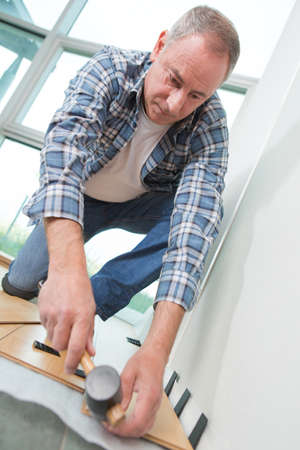tongue and groove: Man using rubber mallet to position laminate flooring