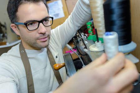 Man changing cotton reel on machine Stock Photo