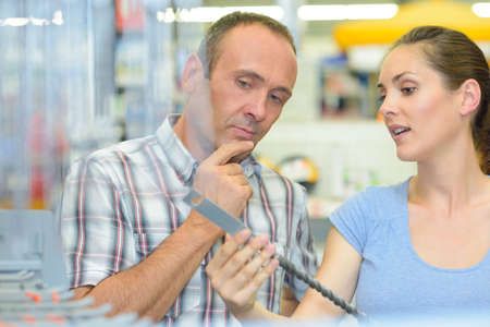 Couple looking at long drill bit Stock Photo