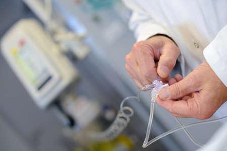 Medical worker adjusting dosage of drip
