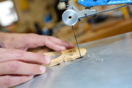 violin making: Closeup of instrument bridge being cut out