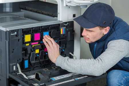 xerox: Man checking ink cartridges in photocopier
