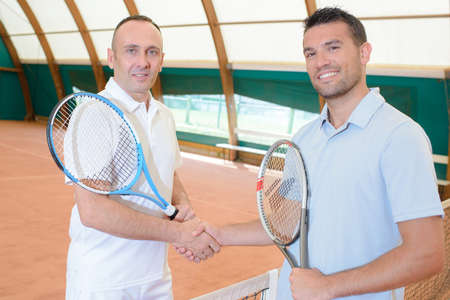 Two men shaking hands on tennis court Stock Photo