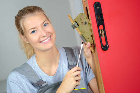 woman locksmith fixing a lock Stock Photo - 71657382
