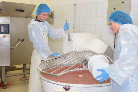 ingredient: Woman pouring ingredient into vat Stock Photo