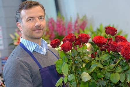 knew: Male florist holding bouquet of red roses