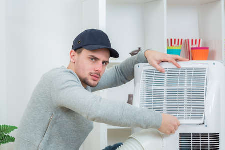 fettler: handsome technician installing air-conditioner in building Stock Photo