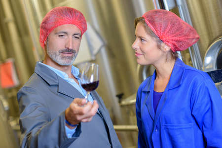 Man and woman in hairnets holding glass of wine Stock Photo