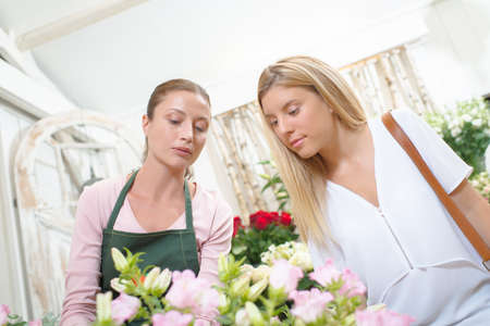 smiling woman in a greenhouse: Florist chatting to a customer