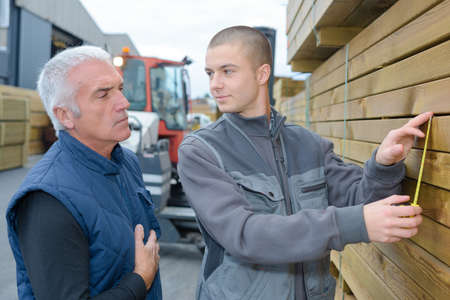 merchant: Men measuring wood in builders yard
