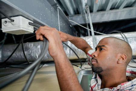 electricidad industrial: electricista de trabajo en el cableado del techo