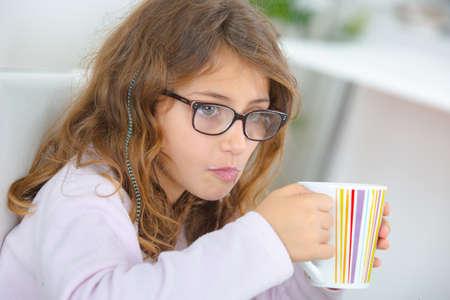 School girl holding stripy cup
