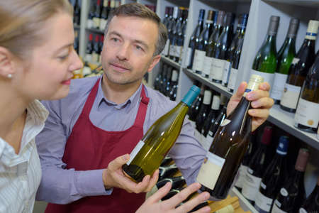 suggesting: Wine merchant suggesting two bottles to customer