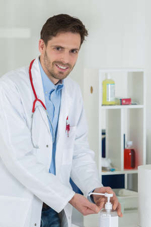sanitizer: medical doctor using sanitizer dispenser in clinic Stock Photo