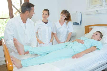 Student nurses watching doctor lift patients leg Фото со стока