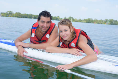 Man and woman laying on surfboard in the water Stock Photo