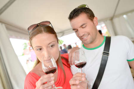 assessing: Couple assessing their glasses of red wine