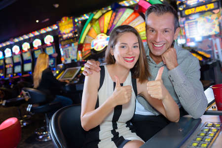 successfull: Couple giving thumbs up in casino