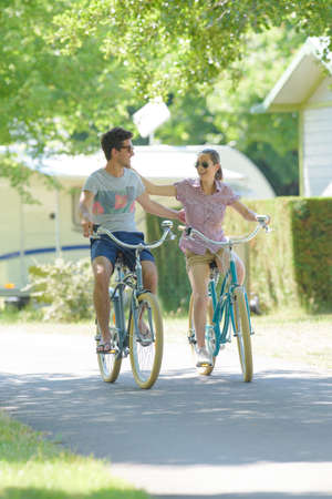 freewheel: Couple cycling arms around each other Stock Photo