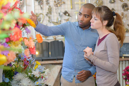 Man and woman looking at memorial flowers Stock Photo