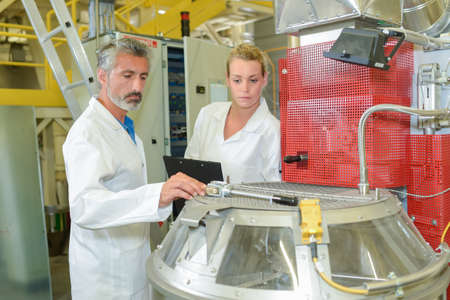 troubleshoot: Male and female technicians checking machinery