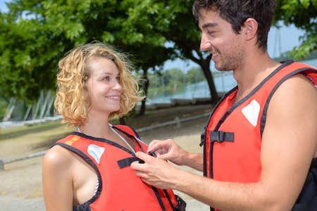boyfriend helping his girlfriend button her safety jacket