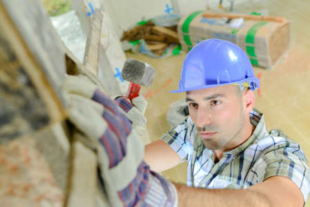 Downward view of builder holding sledge hammer Stock Photo