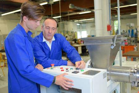 computerised: Man explaining controls of machine to junior worker Stock Photo