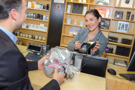 perfumery concept: woman taking payment from man Stock Photo