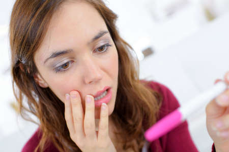 anguished: Anguished woman looking at pregnancy tester