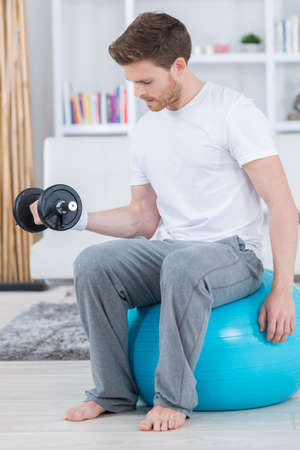 attractive young man with swiss ball doing exercises at home