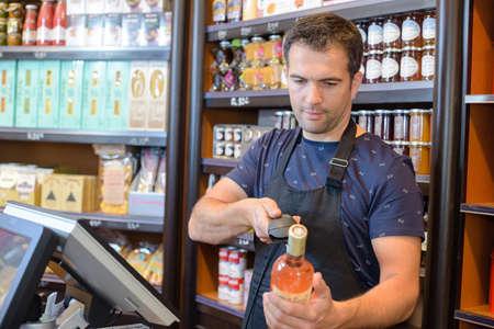 ワインのボトルをスキャン チェック アウト店員 写真素材