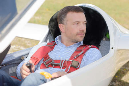 man ready to fly inside the cockpit of a glider Stock Photo