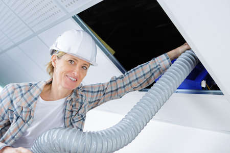 wireman: female worker fitting ventilation system in buildings ceiling