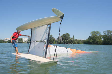 lifevest: salior trying to right his catamaran after capsize