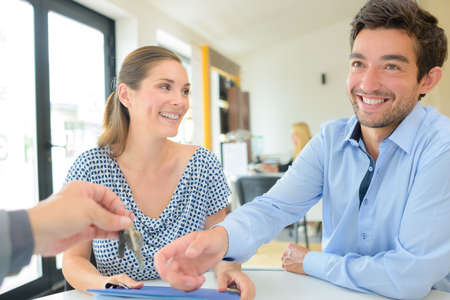 Happy couple receiving keys from estate agent Stock Photo