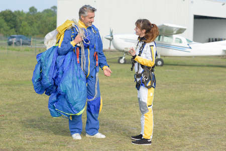 Man and woman in airodrome holding parachute Stock Photo