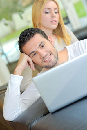Man on laptop, lady looking over his shoulder