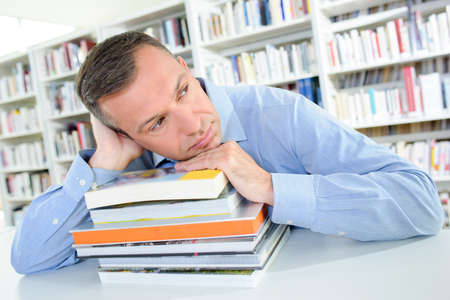 slumped: Man in library slumped on pile of books