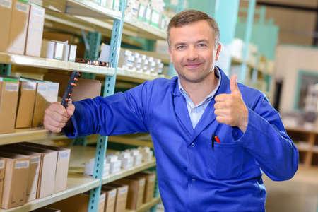 overol: Hombre en almacén hasta la celebración de pulgar