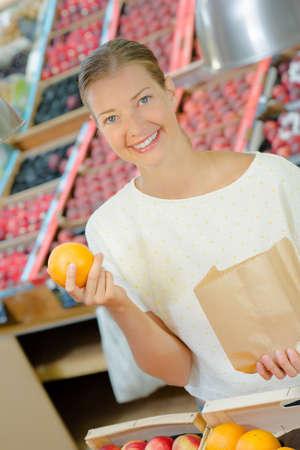 Lady buying oranges, holding paper bag
