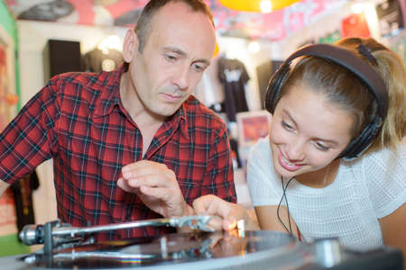 Apprehensive man watching teenager play vinyl record Stock Photo
