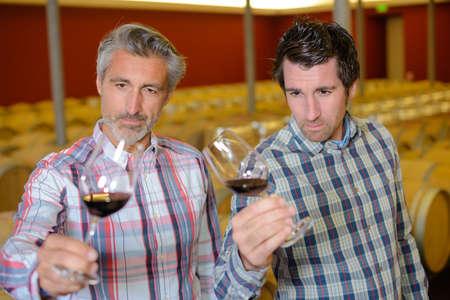 sommeliers: sommeliers tasting wine in a wine cellar