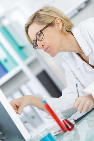 mature female chemist counting stock on computer