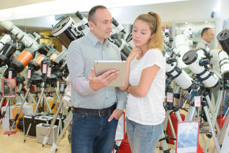 information science: Man holding tablet next to young lady in telescope shop