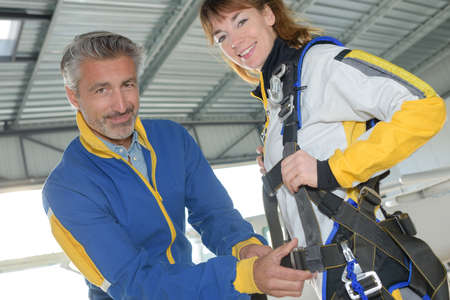 attaching: Man attaching harness onto female skydiver