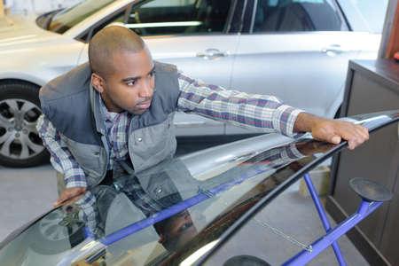 breakable: Mechanic holding windscreen