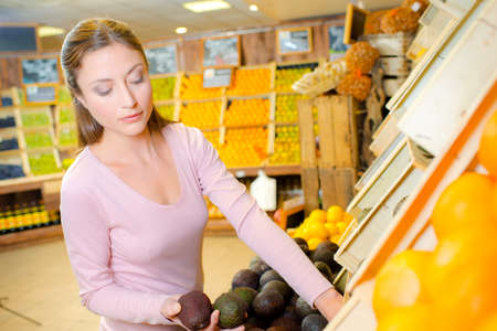firmeza: Lady in greengrocers choosing avocado pears
