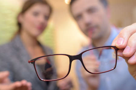 thin wire framed spectacles close focus in optician hands